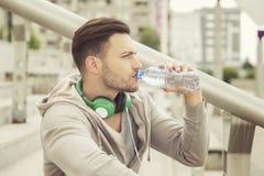 Agua potable del hombre joven y reclinación entre entrenamientos fotos de archivo libres de regalías