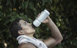 Agua potable del hombre muscular joven de la botella después el suyo que corre o que trabaja al aire libre Imagen de archivo libre de regalías