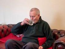 Agua potable del hombre solo en el sofá fotos de archivo