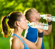 Agua potable del hombre y de la mujer de la botella después Foto de archivo libre de regalías