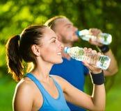 Agua potable del hombre y de la mujer de la botella después Foto de archivo