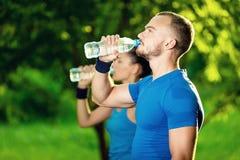Agua potable del hombre y de la mujer de la botella después Fotos de archivo