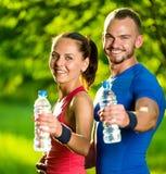 Agua potable del hombre y de la mujer de la botella después del ejercicio del deporte de la aptitud Foto de archivo