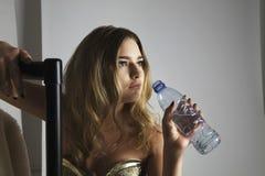 Agua potable del modelo de moda de la botella en estudio Fotos de archivo