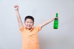 Agua potable del muchacho asiático de la botella verde Fotografía de archivo