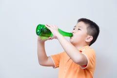 Agua potable del muchacho asiático de la botella verde Fotografía de archivo libre de regalías