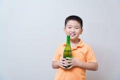 Agua potable del muchacho asiático de la botella verde Imagenes de archivo