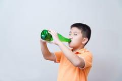 Agua potable del muchacho asiático de la botella verde Foto de archivo