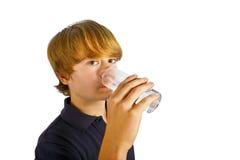 Agua potable del muchacho fuera de un vidrio Fotografía de archivo