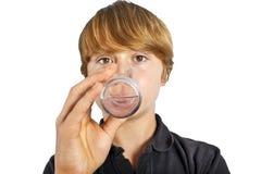 Agua potable del muchacho fuera de un vidrio Fotografía de archivo libre de regalías