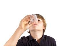 Agua potable del muchacho fuera de un vidrio Fotos de archivo libres de regalías