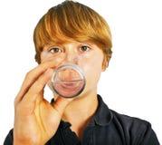 Agua potable del muchacho fuera de un vidrio Foto de archivo
