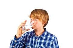 Agua potable del muchacho fuera de un vidrio Fotos de archivo