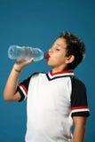 Agua potable del muchacho sediento Fotografía de archivo