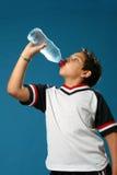 Agua potable del muchacho sediento Foto de archivo
