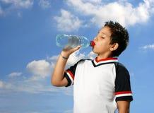Agua potable del muchacho sediento hacia fuera Fotos de archivo