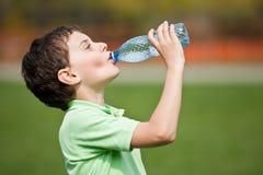 Agua potable del niño foto de archivo