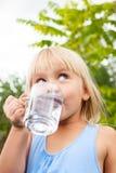 Agua potable del niño al aire libre imagen de archivo