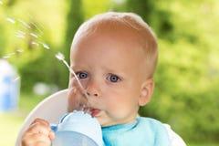 Agua potable del niño divertido lindo Un bebé del año hace una corriente del agua con su boca Fotografía de archivo libre de regalías