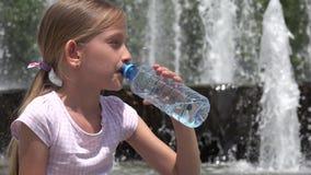 Agua potable del niño en el parque, opinión sedienta del retrato de la muchacha por la fuente 4K al aire libre metrajes