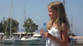 Agua potable del niño en el puerto de la playa, muchacha turística feliz en las vacaciones de verano 4K metrajes