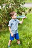 Agua potable del niño en naturaleza Fotos de archivo libres de regalías