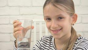 Agua potable del niño, niño sediento que estudia el vidrio del agua dulce, muchacha en cocina foto de archivo