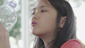 Agua potable del ni?o de la botella Chica joven con la botella de agua a disposición en restaurante almacen de video