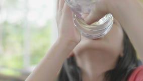 Agua potable del ni?o de la botella Chica joven con la botella de agua a disposici?n en restaurante almacen de video