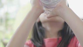 Agua potable del ni?o de la botella Chica joven con la botella de agua a disposici?n en restaurante metrajes