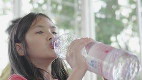 Agua potable del ni?o de la botella Chica joven con la botella de agua a disposici?n en restaurante almacen de metraje de vídeo