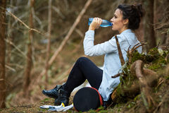 Agua potable del trekker de la mujer en el bosque foto de archivo