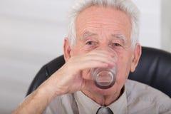 Agua potable del viejo hombre Fotografía de archivo libre de regalías