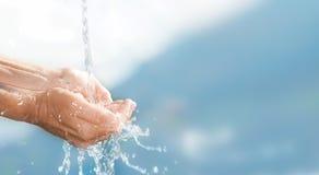 Agua potable en manos fotos de archivo