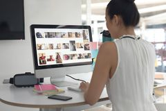 Agua potable femenina del diseñador gráfico mientras que trabaja en el ordenador en el escritorio en una oficina moderna fotografía de archivo