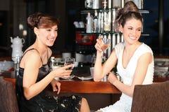 Agua potable hermosa de dos mujeres jovenes en la barra Fotografía de archivo libre de regalías