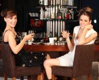 Agua potable hermosa de dos mujeres jovenes en la barra Fotos de archivo libres de regalías