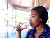 Agua potable joven de la mujer de negocios foto de archivo libre de regalías