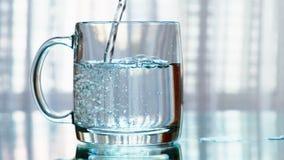 Agua potable limpia que es vertida en una taza Cámara lenta metrajes