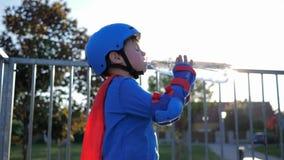 Agua potable, niño de Rollerblading en casco con la botella plástica en la mano al aire libre almacen de metraje de vídeo