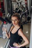 Agua potable rubia hermosa en el gimnasio Imágenes de archivo libres de regalías