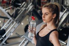 Agua potable rubia hermosa en el gimnasio Fotos de archivo