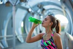 Agua potable sana de la mujer joven y el escuchar la música después de ejercitar Fotos de archivo libres de regalías
