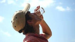 Agua potable sana del hombre joven del aire libre de cristal contra el cielo Cámara lenta 1920x1080 metrajes