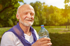 Agua potable sedienta del hombre mayor Fotos de archivo libres de regalías