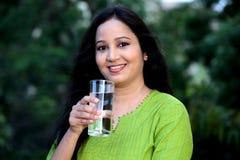 Agua potable sonriente de la mujer joven en al aire libre Imágenes de archivo libres de regalías
