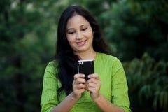 Agua potable sonriente de la mujer joven en al aire libre Fotografía de archivo libre de regalías