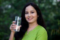 Agua potable sonriente de la mujer joven en al aire libre Imagen de archivo libre de regalías