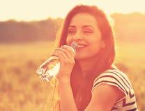 Agua potable sonriente feliz de la mujer de la botella en bri del verano Imagenes de archivo