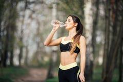 Agua potable sonriente joven de la mujer de la botella después del ejercicio del deporte de la aptitud al aire libre en parque Imagenes de archivo